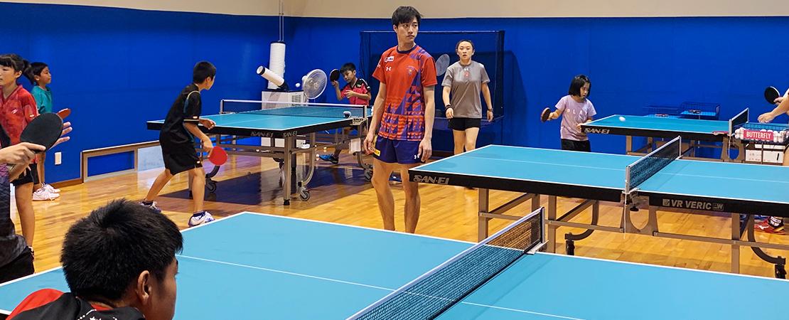 卓球場にいる江 宏傑ジュニア監督の写真